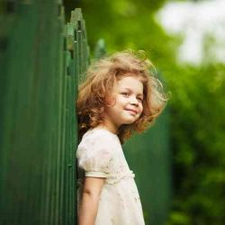 Happy, cheerful and shaggy little girl in a dress